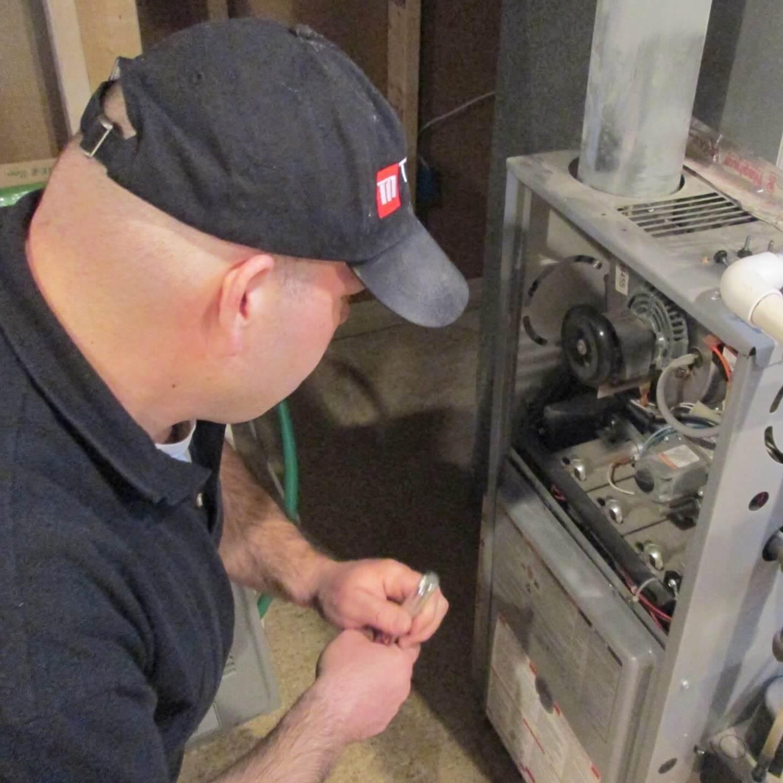 A Home inspector examine a furnace